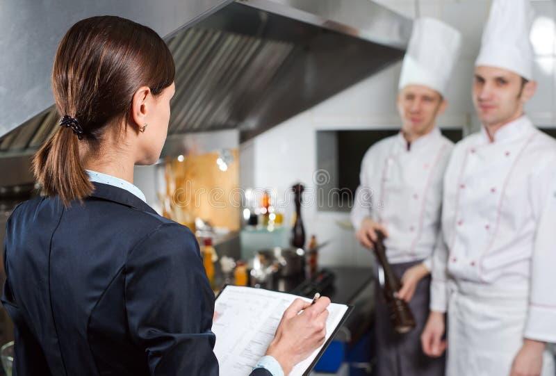 Restauracyjny kierownik informuje jego kuchenny personel w handlowej kuchni zdjęcia stock