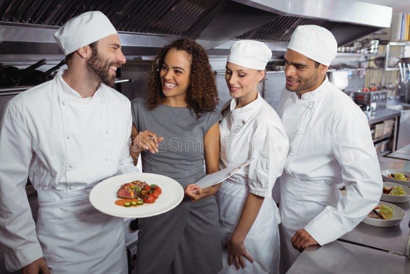 Restauracyjny kierownik oddziała wzajemnie z jego kuchennym personelem obraz royalty free