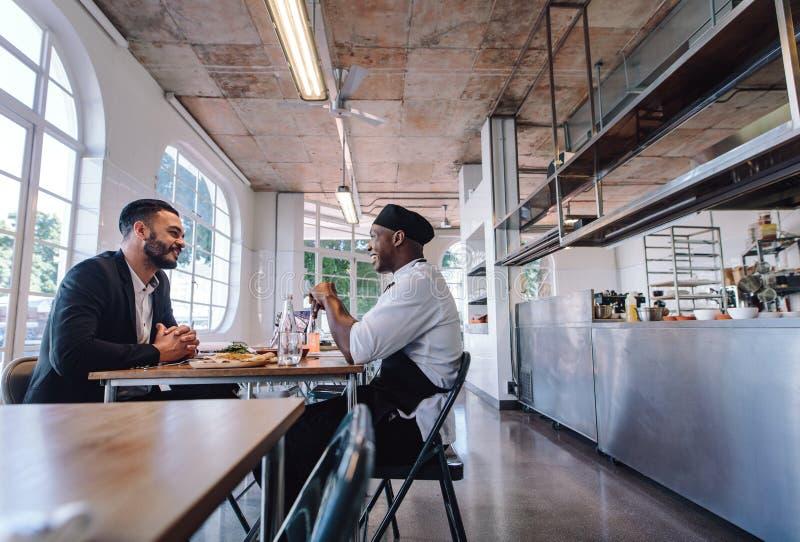 Restauracyjny kierownik opowiada z fachowym szefem kuchni fotografia royalty free