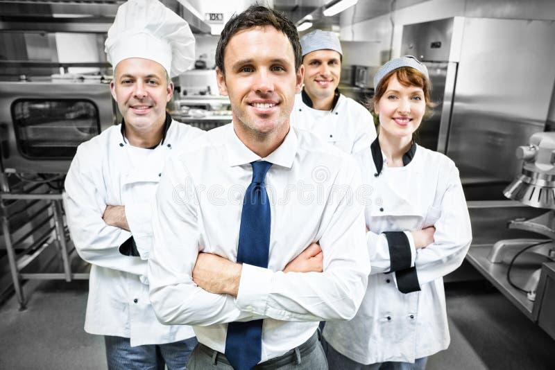 Restauracyjny kierownik pozuje przed drużyną szefowie kuchni zdjęcia stock