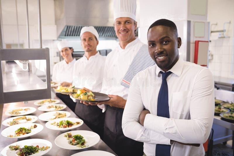 Restauracyjny kierownik z jego kuchennym personelem obraz stock