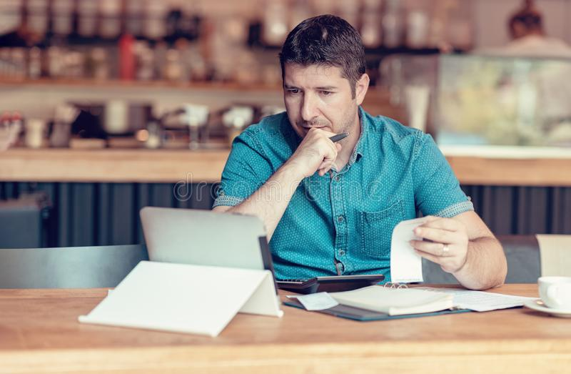 Restaurangägare som kontrollerar månatliga rapporter på en minnestavla, räkningar och kostnader av hans små och medelstora företa arkivbilder
