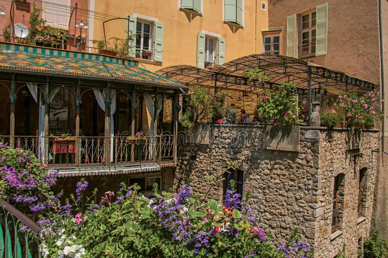 Restaurang med blommor och stenväggar i den älskvärda byn av Moustiers-Sainte-Marie arkivfoto
