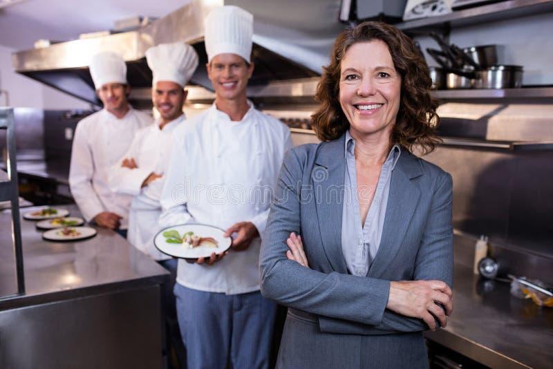 Restaurangchef som framme poserar av laget av kockar arkivbilder