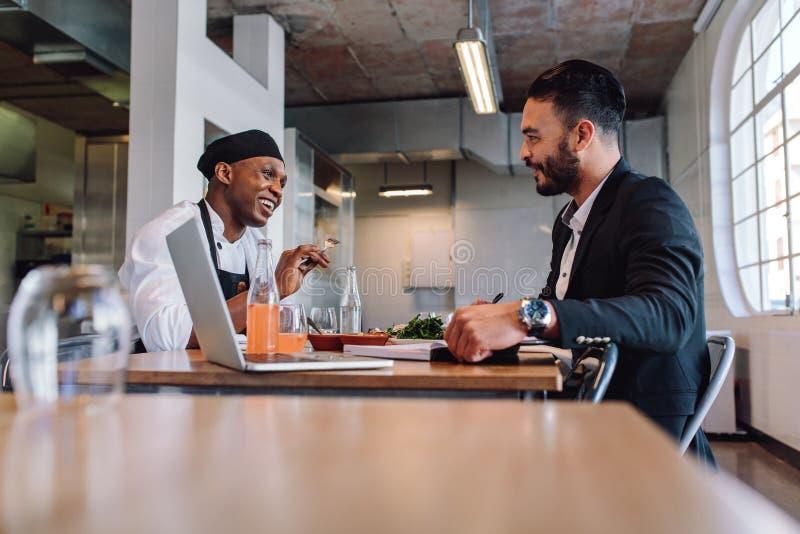 Restaurangchef som har en konversation med kocken royaltyfri foto