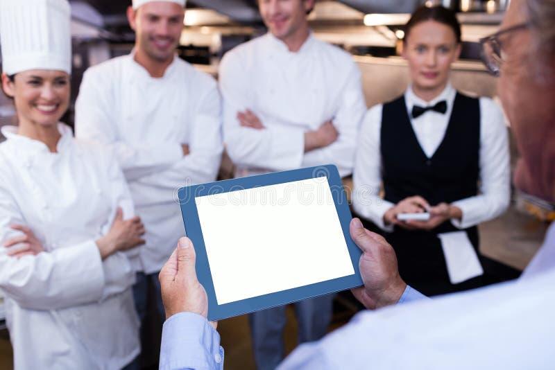 Restaurangchef som sammanfattar till hans kökpersonal royaltyfria bilder