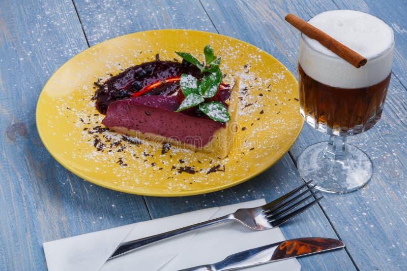 Restaurangefterrätt Bärostkaka med kräm- sodavatten på blått trä arkivbilder