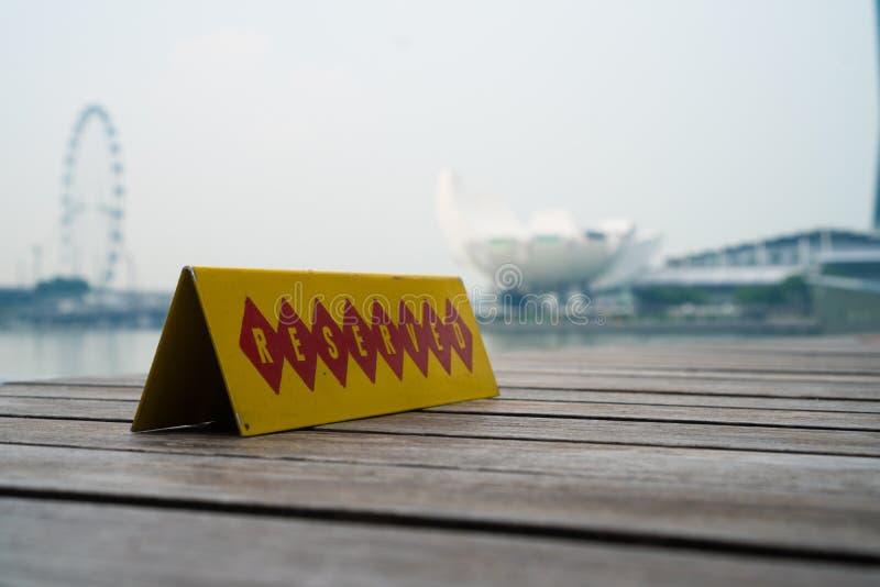 Restaurangen reserverade tabelltecknet med det Singapore landskapet i bakgrunden royaltyfri foto
