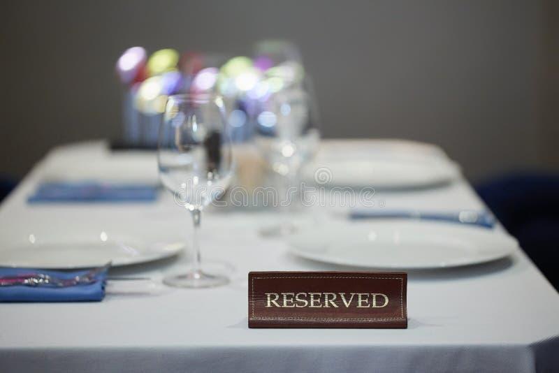 Restaurangen reserverade tabelltecknet med st?lleinst?llningen och vinexponeringsglas som var klara f?r ett parti royaltyfri bild