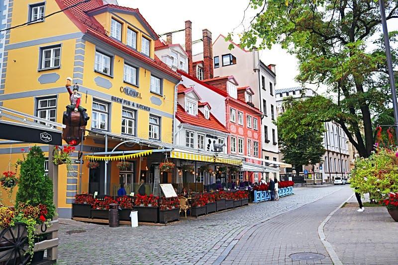 Restauranger och färgrika byggnader på den Meistaru gatan i den gamla staden, Riga royaltyfri fotografi