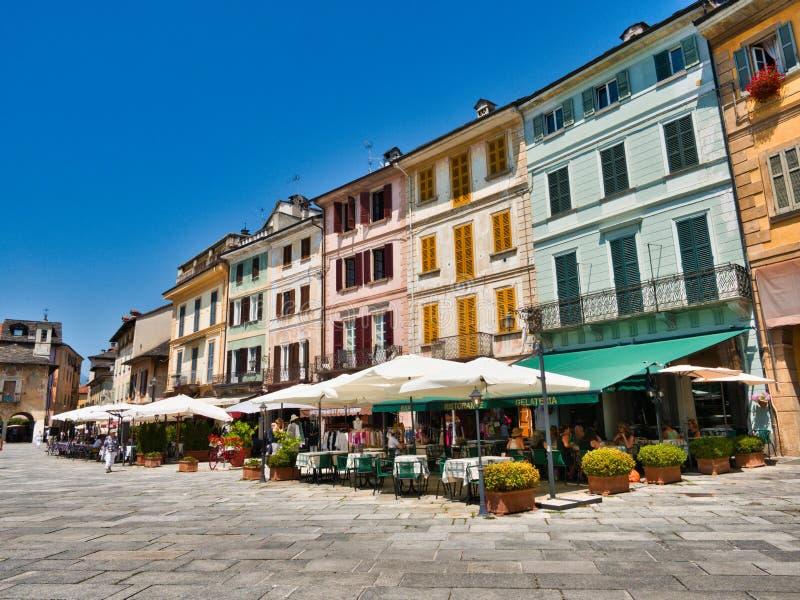 Restauranger och lokala affärer i piazza Motta i byn av Orta San Giulio Italien under en sommarmorgon arkivbild