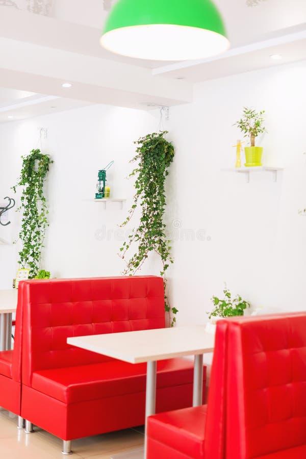 Restauranginre för modern design i vita och röda färger med växter royaltyfri bild