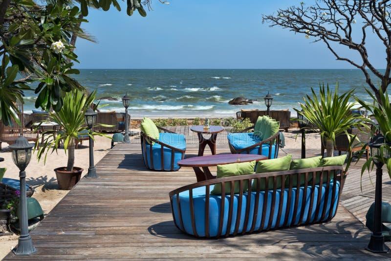 Restaurangstolar och kuddar mot havet arkivbilder