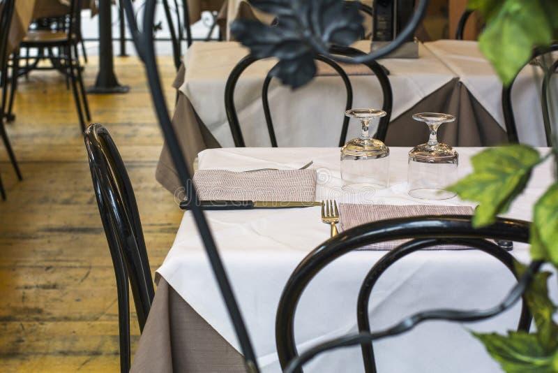 Restaurangtabell med den vitt bordduken och bestick arkivbild