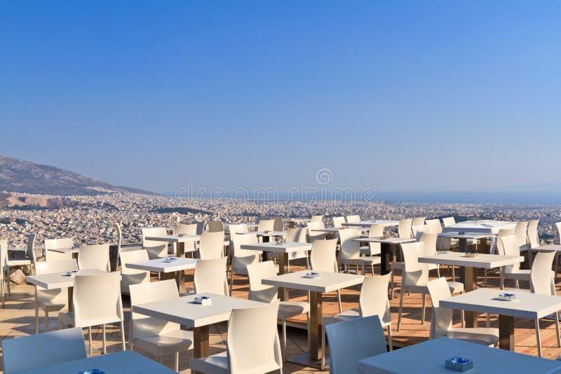 Restaurangtabeller med panoramautsikt av den athens staden royaltyfri bild