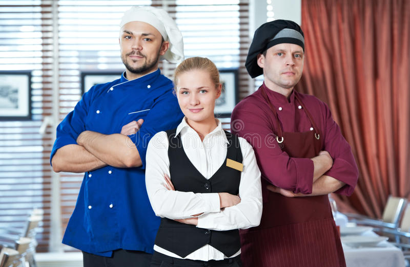 Restaurant administrator and chefs. Waitress girl administrator and chefs of commercial restaurant in uniform royalty free stock photo