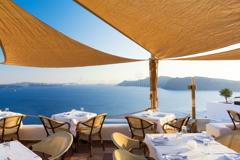 Restaurant auf Terrasse mit Ansicht über Meer, Santorini-Insel, die Kykladen, Griechenland stockfotografie
