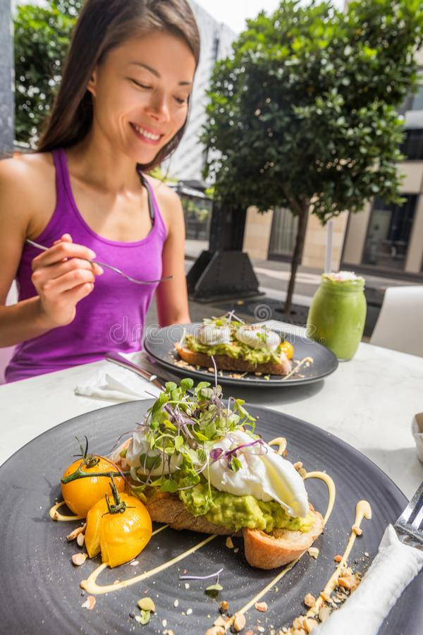 Restaurant breakfast brunch avocado toast with eggs woman eating plate at cafe. Two meals couple enjoying morning together on royalty free stock photo