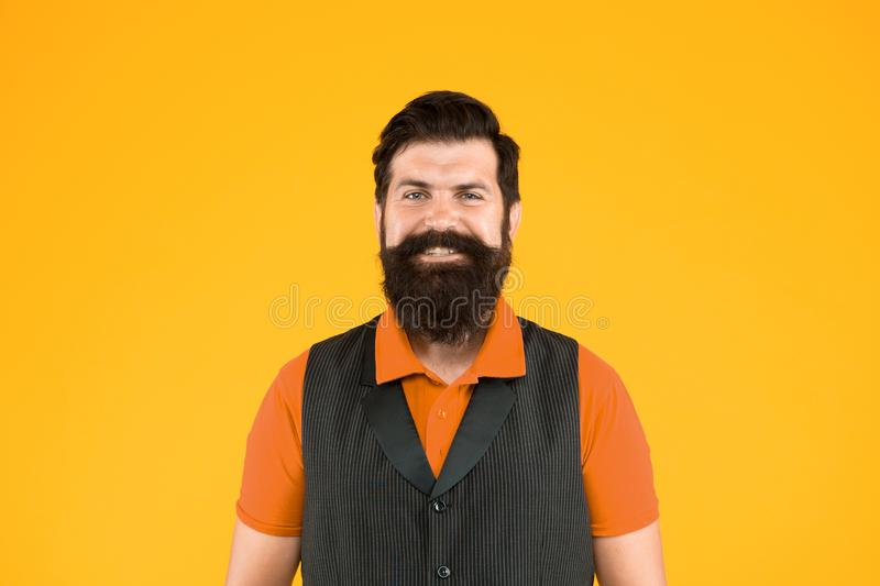 Restaurant cafe staff wanted. Man bearded hipster with mustache wear vest and shirt uniform yellow background. Shop. Staff concept. Salesman cashier career royalty free stock photo