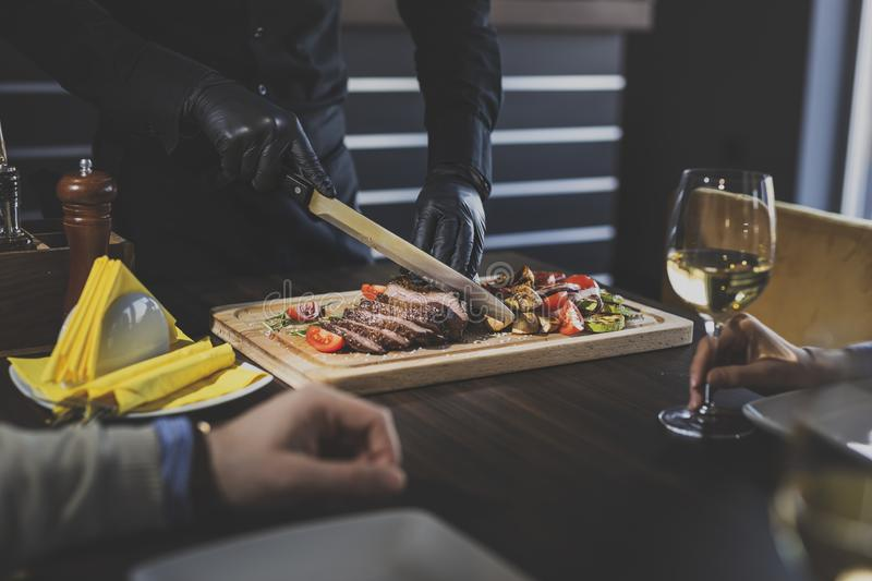 Restaurant chef slicing steak. Restaurant chef slicing medium rare beef steak and serving the specialty of the house to guests royalty free stock photo