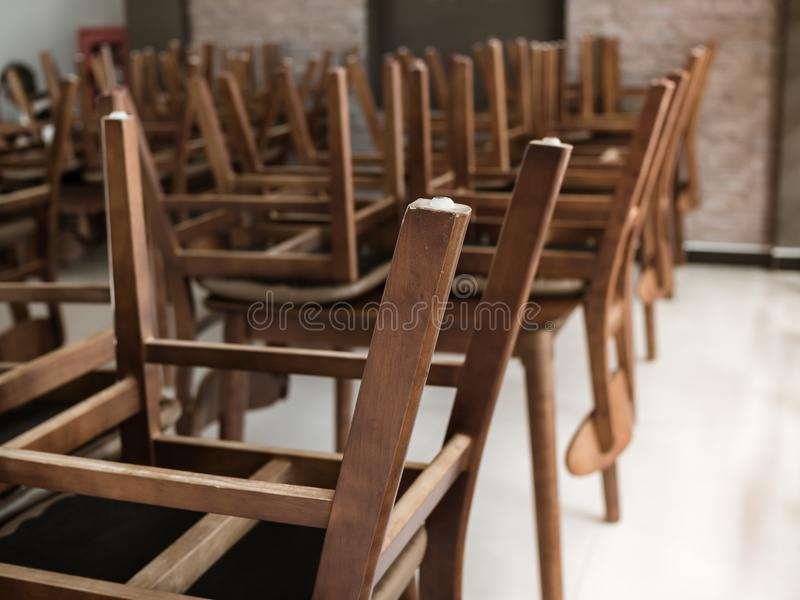 Restaurant Closed. Wooden Chairs areUpside Down On Wooden Table in Restaurant for Cleaning Floor royalty free stock image