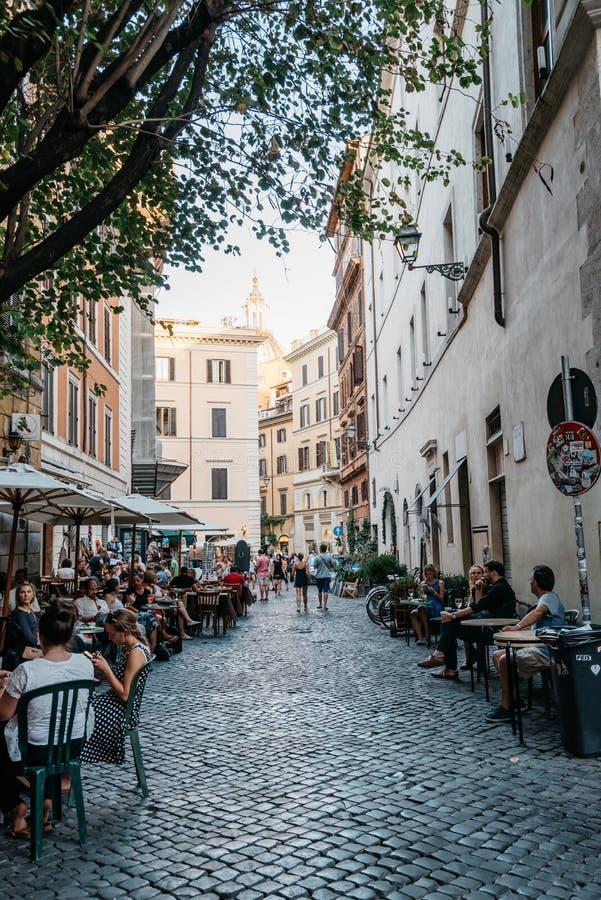 Restaurant de trottoir avec des touristes dans la rue romaine par été ensoleillé images stock