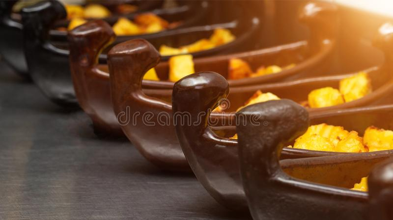 Restaurant dish of a boat with potatoes in a golden crust fried in a deep fryer. close-up, sun royalty free stock image
