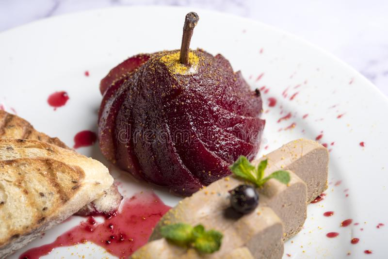 Restaurant dish of haute cuisine top view. Seared foie gras served with berry sauce and pink pear on black slate plate. French delicatessen meal, roasted goose royalty free stock image