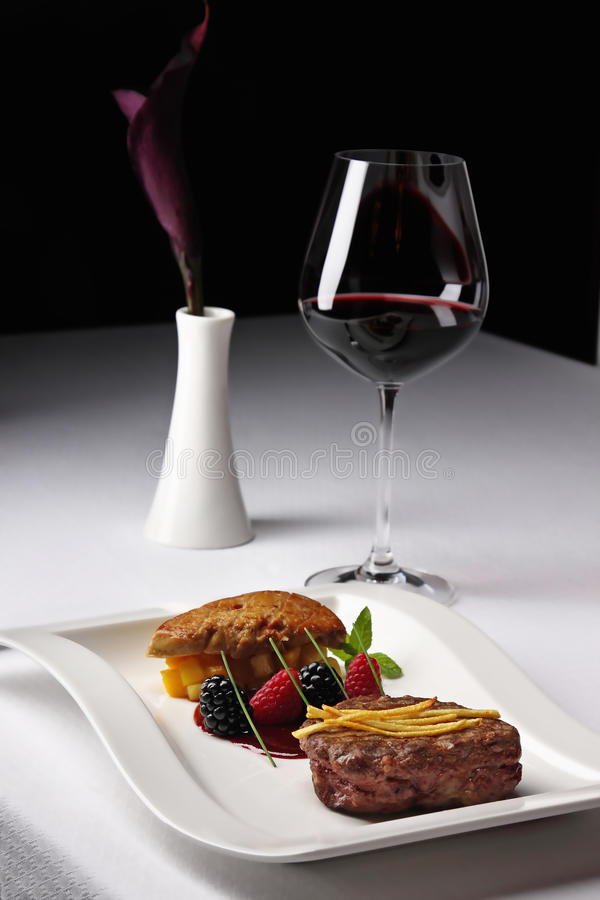 Restaurant dish with red wine. Meat dish with red wine and calla lily on the table royalty free stock images