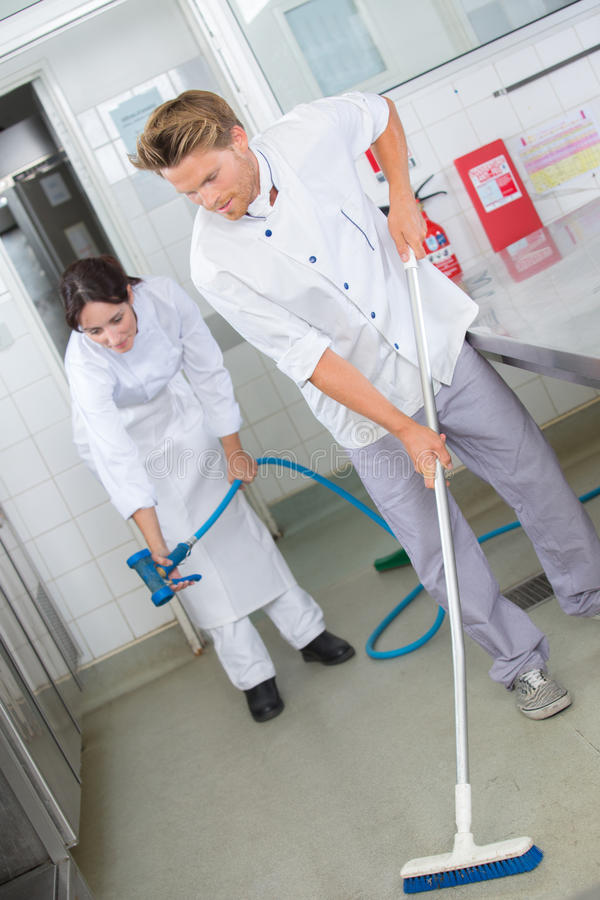 Restaurant employees cleaning kitchen floor. Restaurant employees cleaning the kitchen floor royalty free stock images