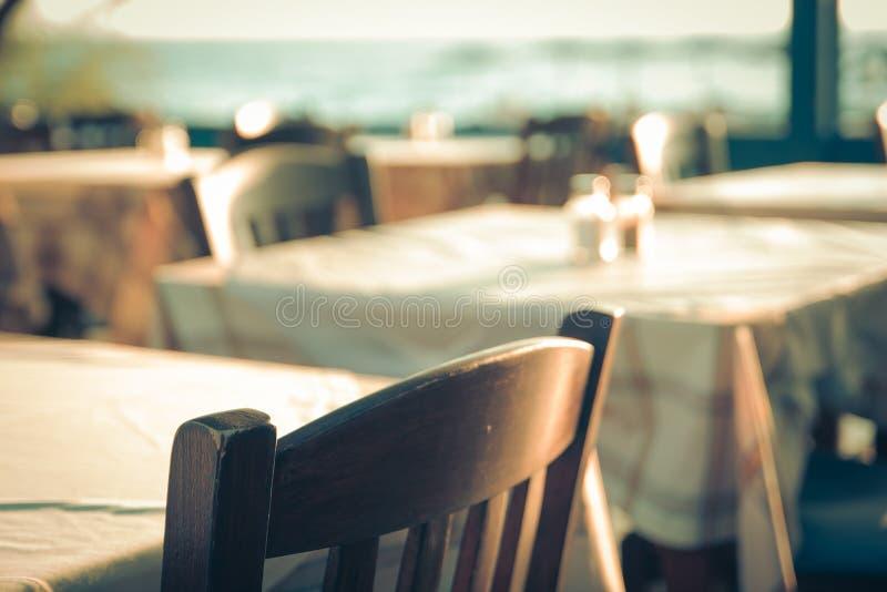 Restaurant extérieur grec traditionnel sur la terrasse donnant sur la mer Méditerranée (Grèce) table vide à une mer de rue photographie stock libre de droits