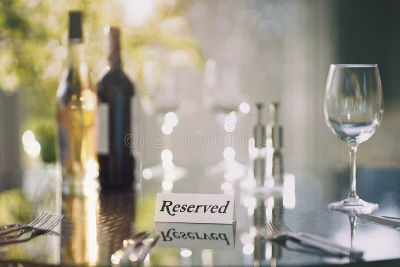 Restaurant gereserveerd tafelteken met plaatsbepaling en wijnbril klaar voor een partij stock afbeelding