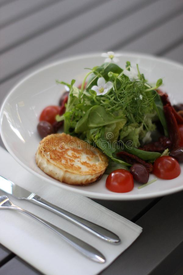 Restaurant goat cheese salat with cherry tomatoes. European cuisine restaurant goat cheese salat with cherry tomatoes garnished with common wood sorrel royalty free stock photography