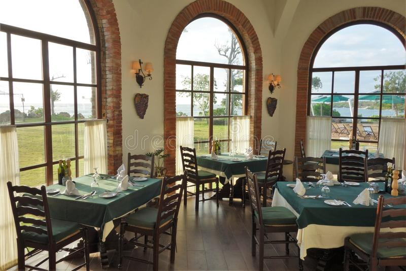 Restaurant with Grand Window View of lush green and blue seas. Restaurant with green tables and wooden chairs with grand arched window view of outdoor lush green royalty free stock photography