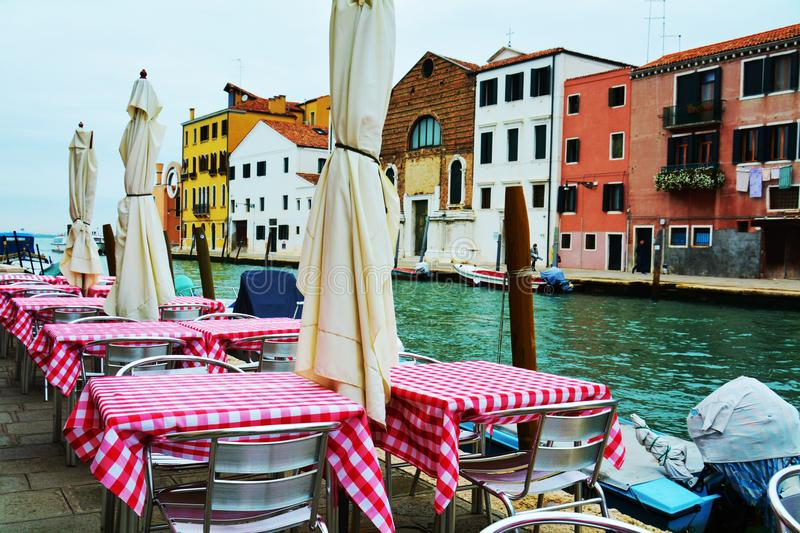 Restaurant and historical buildings, in Venice, Italy. Historical buildings and elegant restaurant with colorful tables, outdoors, in Venice, Italy, Europe royalty free stock photos