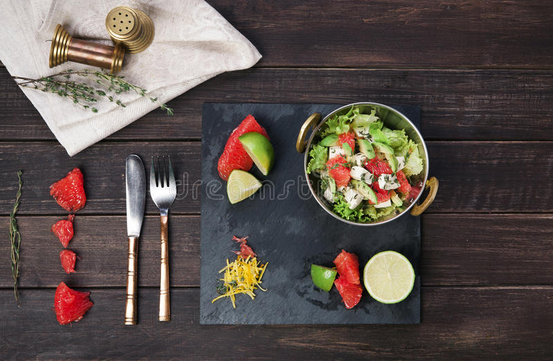 Restaurant indian food, vegetarian salad. Vegetarian restaurant food. Indian salad with tofu and grapefruit served in copper bowl on wooden table, top view royalty free stock photo