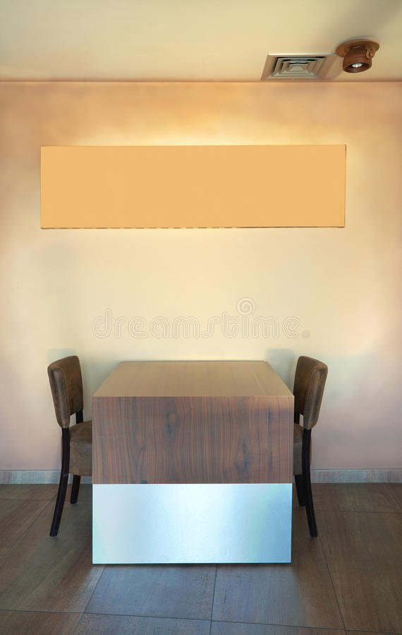 Restaurant interior. Table and chairs in a restaurant with empty frame on the wall royalty free stock images
