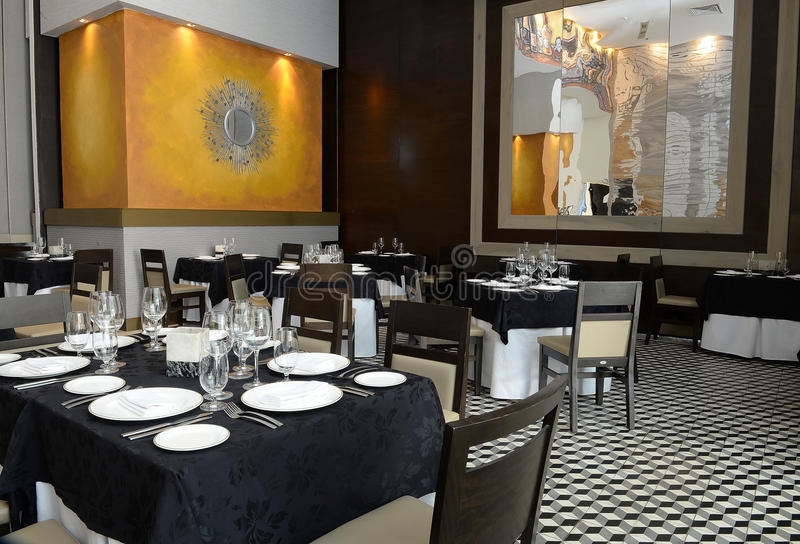 Restaurant interior. Interior of empty modern restaurant with black and white table clothes and checkered tile flooring stock image