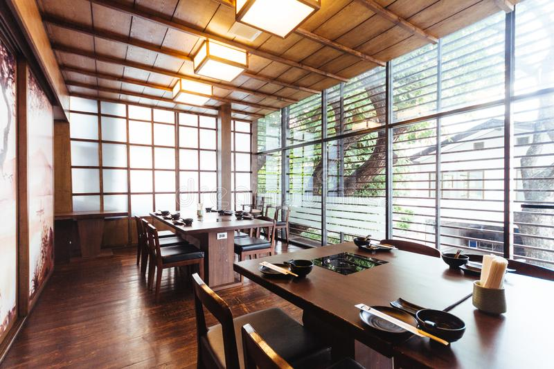 Restaurant japonais avec en bois décoré Grand vitrail pour la lumière naturelle Lumineux et confortable avec des tables et des si photographie stock libre de droits