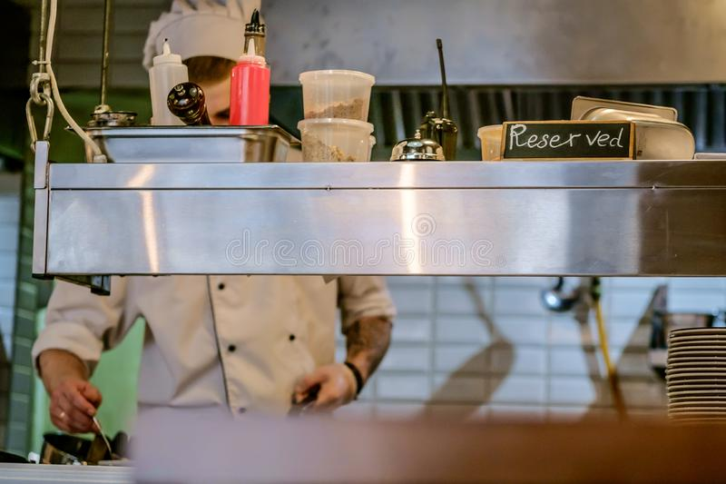 restaurant kitchen close up with Reserved table and blurred chief cook on the background. stock image