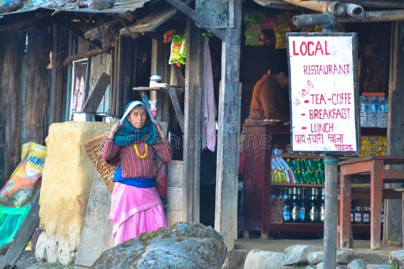 Restaurant local, femme avec le panier, village Népal de trekking photographie stock libre de droits