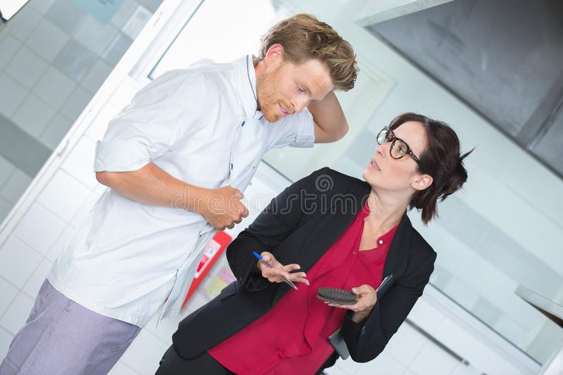 Restaurant manager talks to chef about reservations royalty free stock images