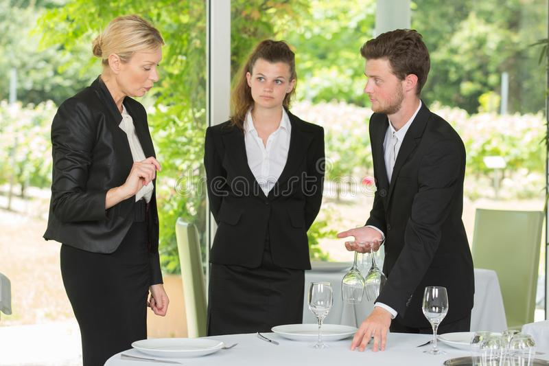 Restaurant manager with young workers stock images