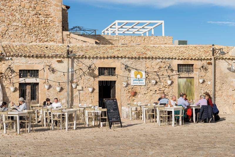 Restaurant in Marzamemi Village - Sicily island Italy. MARZAMEMI, SICILY ISLAND, ITALY, DEC 10, 2017: Tourists and locals sitting at a typical restaurant in the royalty free stock photos