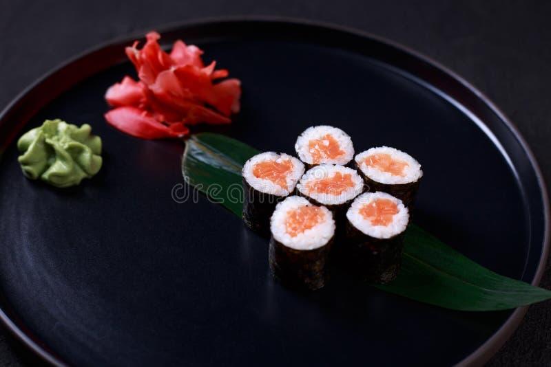 Salmon maki sushi rolls served on black plate stock photo