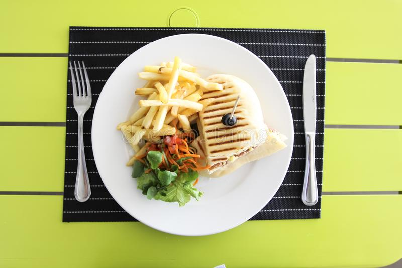 French fries with bread and salad. Table setting in a restaurant royalty free stock image