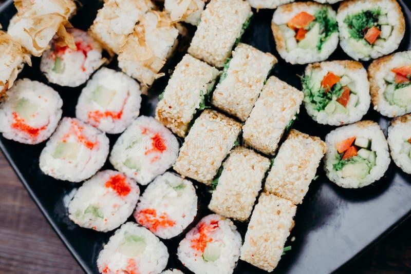 Sushi set, served on black plate, food background stock photography