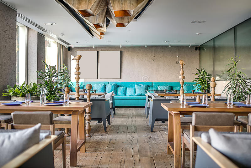 Restaurant in modern style. Modern restaurant with concrete walls and parquet on the floor. There are sofas with pillows, tables, chairs, wooden poles with birds stock photo
