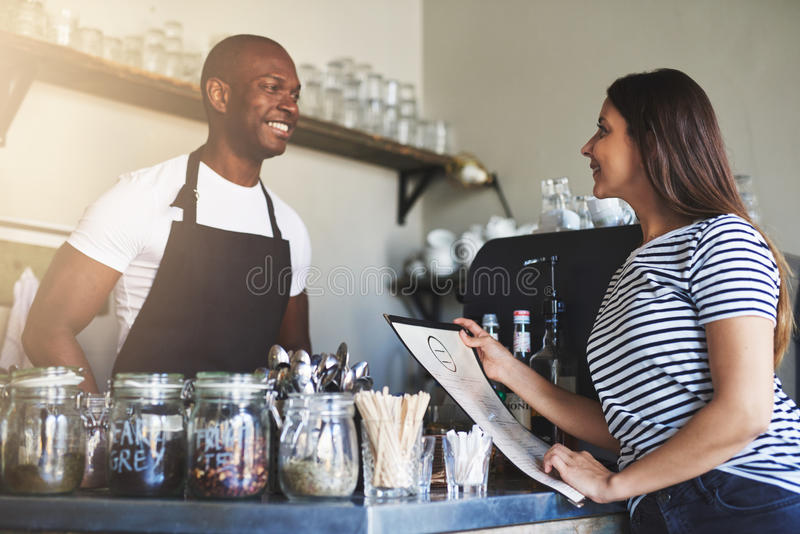 Restaurant owner talking with customer. Handsome young Black restaurant owner in apron talking with cheerful female customer in striped shirt holding menu at stock photography
