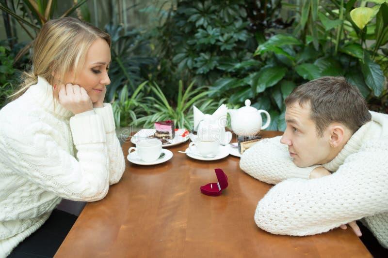 Restaurant, paar en vakantieconcept - opgewekte jonge vrouw die vriend met verlovingsring bekijken royalty-vrije stock foto's